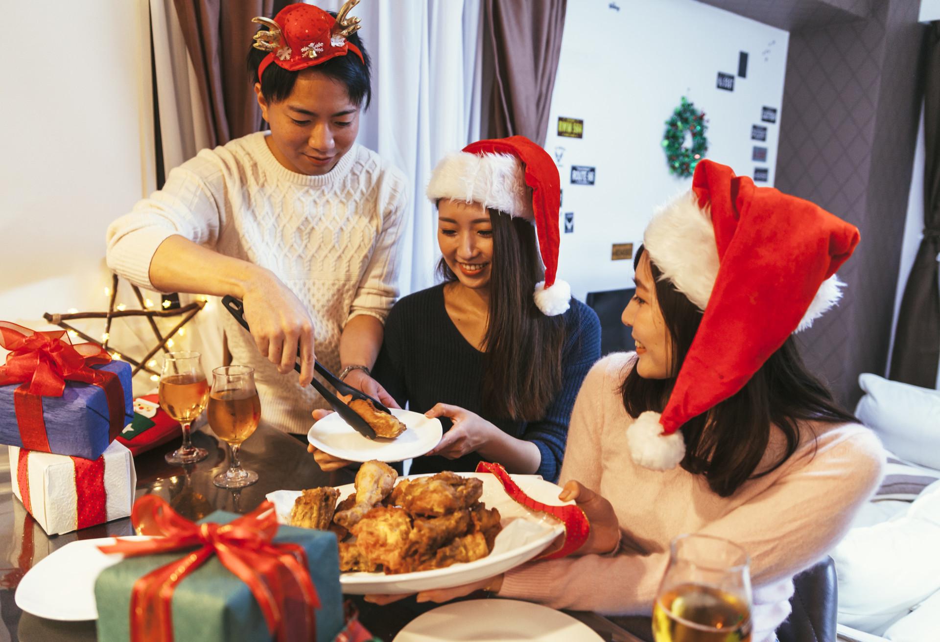 Una familia está preparada para meterle mano al cubo de pollo frito de KFC, una de las tradiciones navideñas japonesas más extrañas que te puedes encontrar.